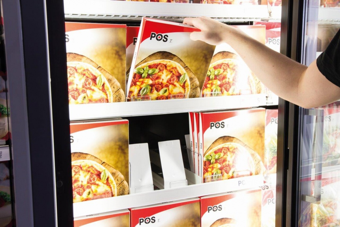 One hand grabs a frozen pizza from the chiller cabinet...