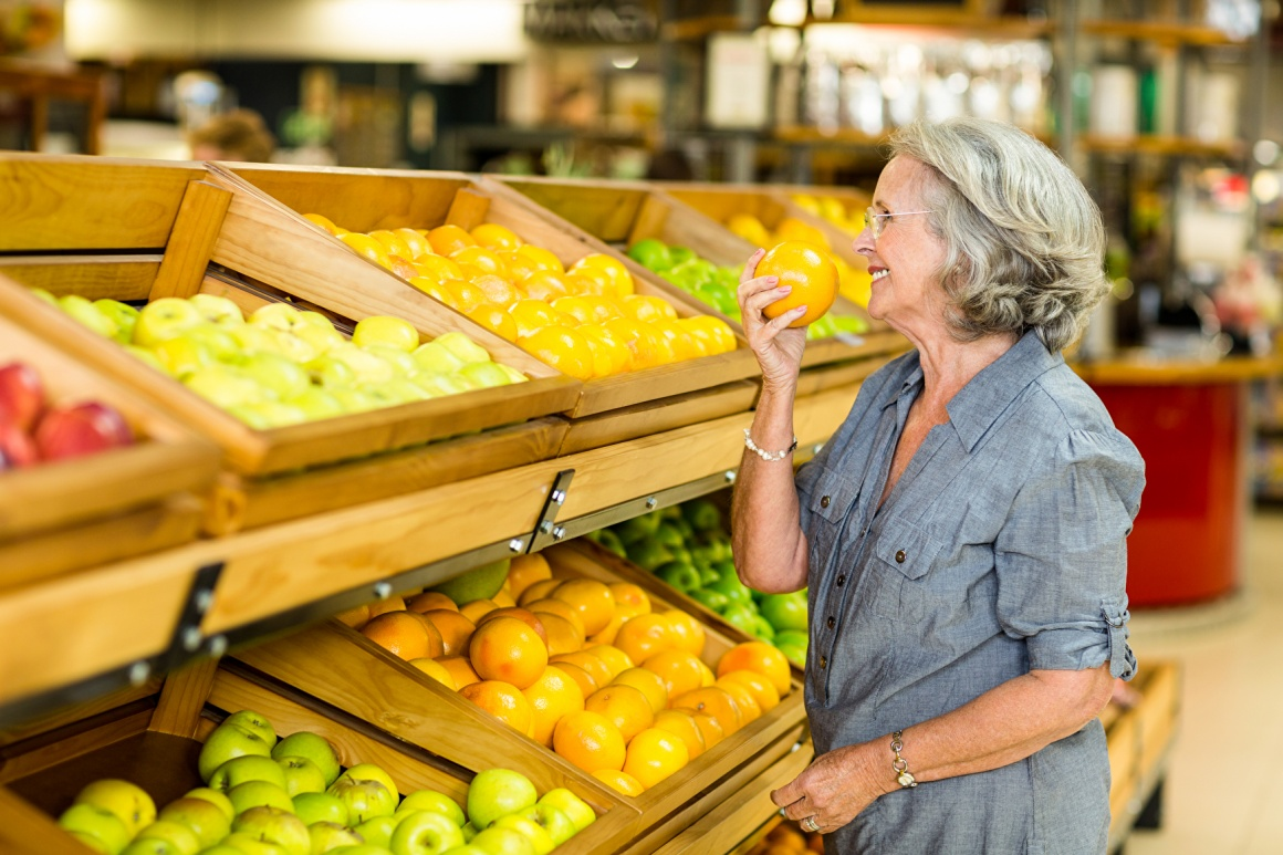 Older woman standing in front of a fruit shelf in the supermarket and smelling...