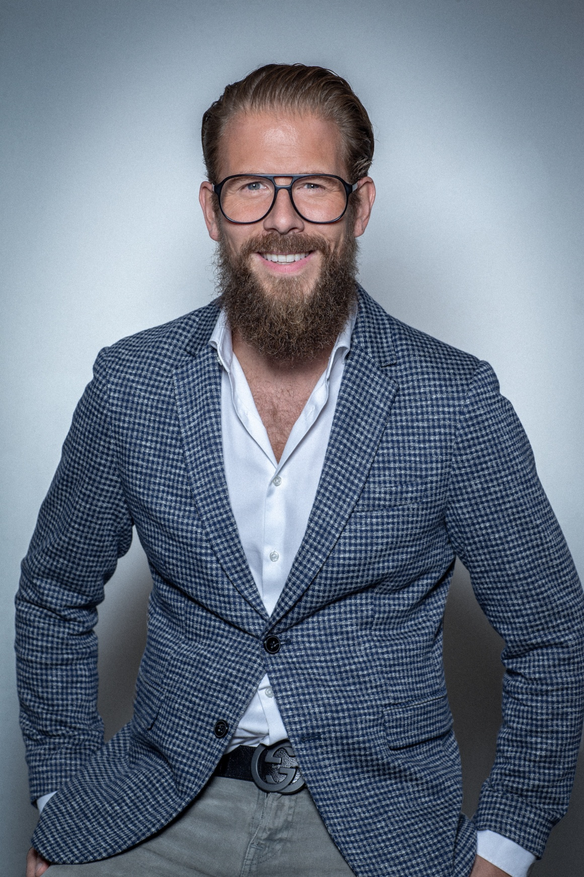 A man in a jacket with beard and glasses