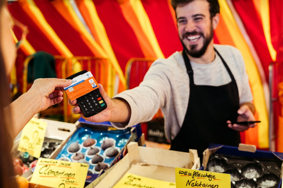 A fruit and vegetable retailer at a market stand holds out a mobile payment...