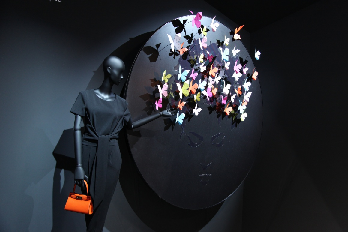 Paper butterflies on the wall next to a mannequin