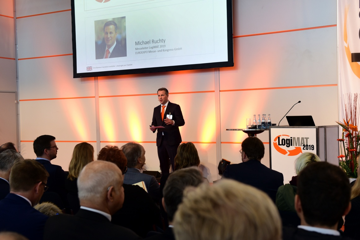 Man speaks on a stage at LogiMAT