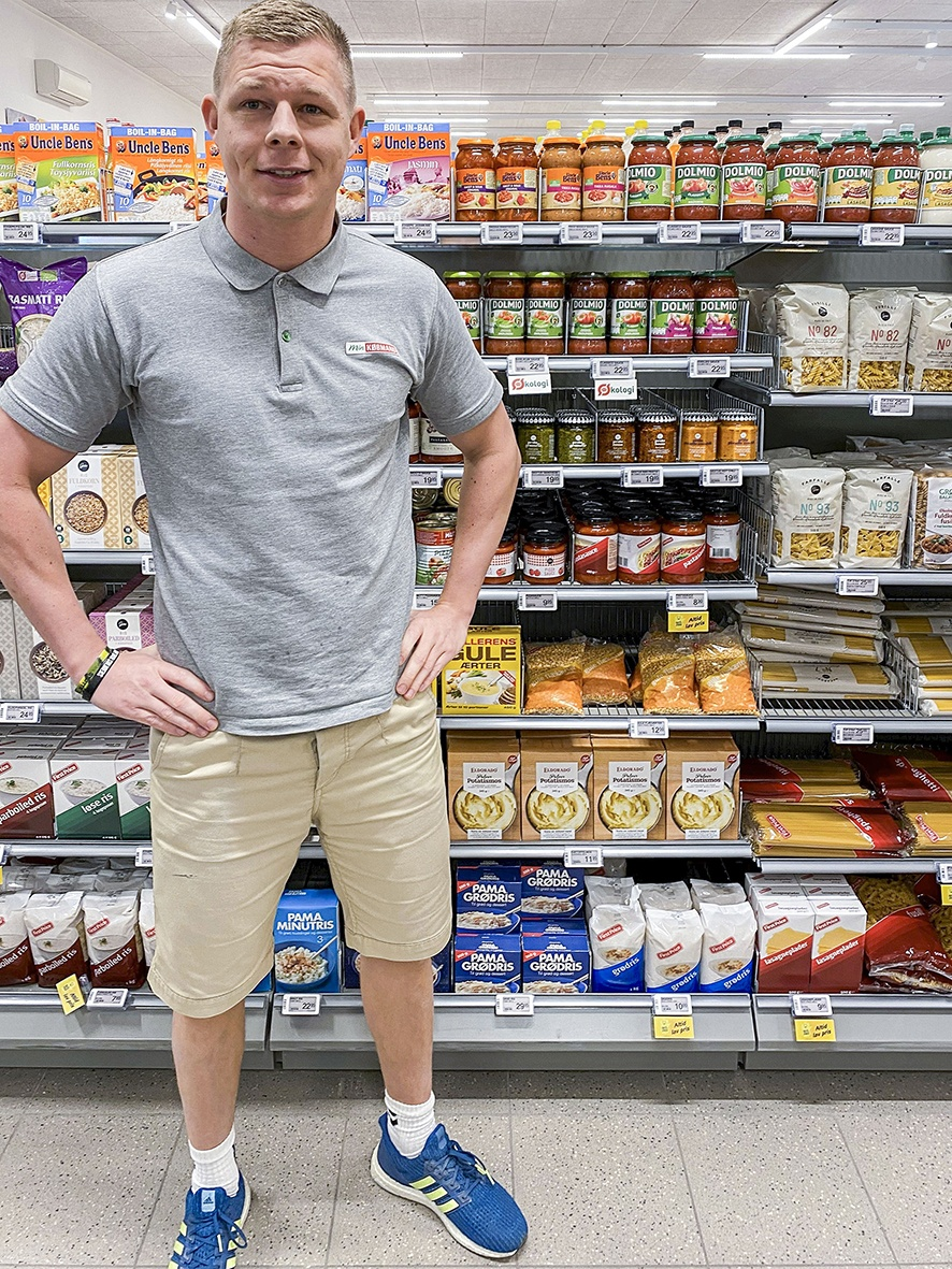 A young man standing in a small store in front of a food shelf...