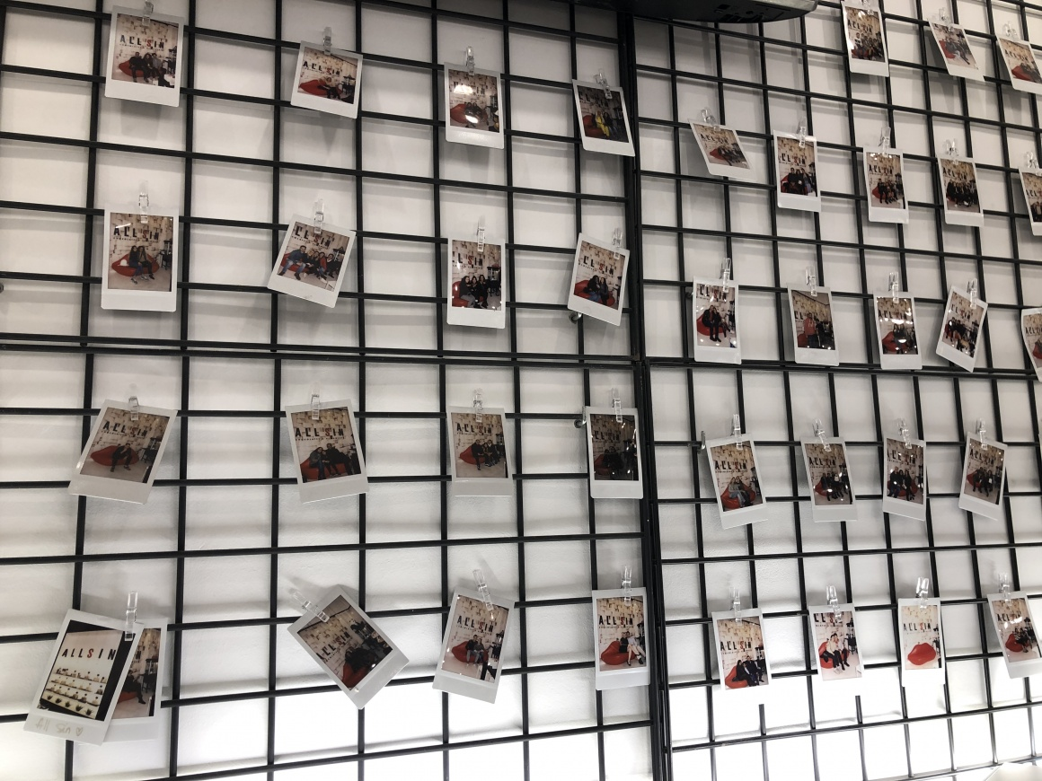 A black grid in front of a white wall with Polaroid photos hanging from it...
