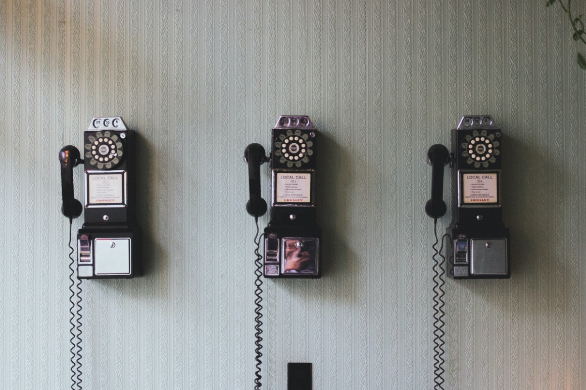 3 old telephones hanging on a wall