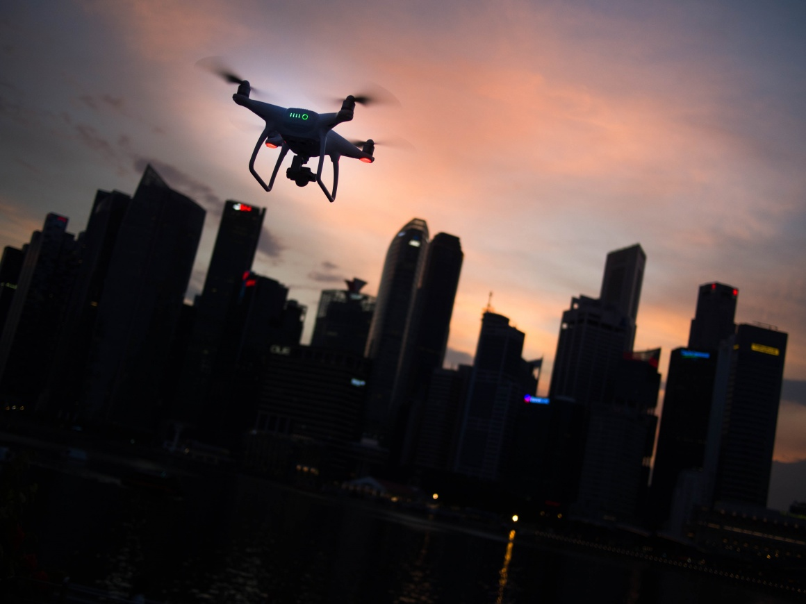 A drone in front of a dark city skyline