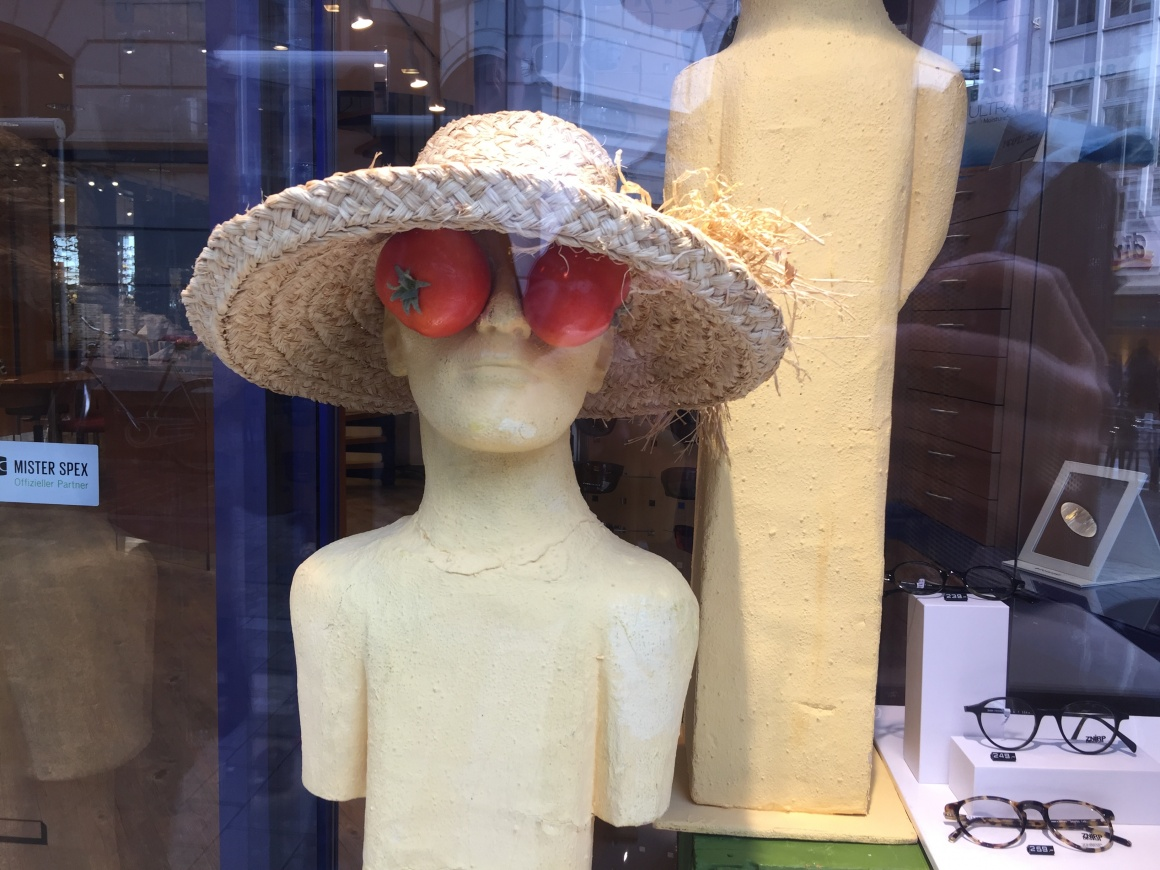 A mannequin with straw hat and tomatoes over its eyes, glasses displayed next...