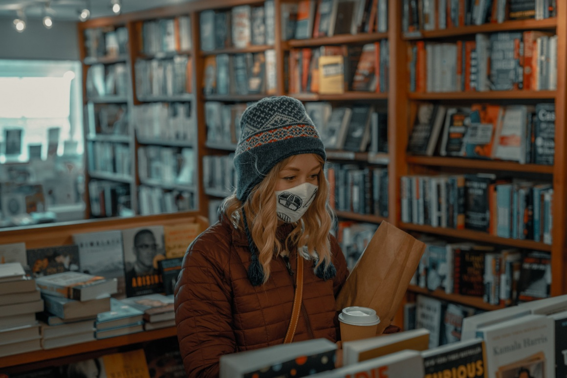 A woman wearing a mask shopping in a book store; copyright: Clay Banks/Unsplash...